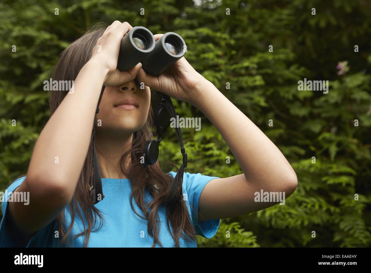Une jeune fille avec l'observation des oiseaux des jumelles. Photo Stock