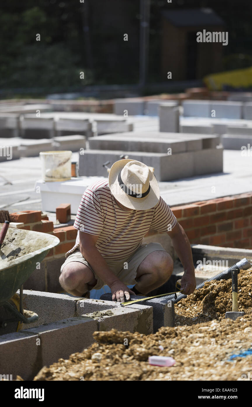 Un homme travaillant sur un chantier de construction, de poser les fondations d'un bâtiment. Photo Stock