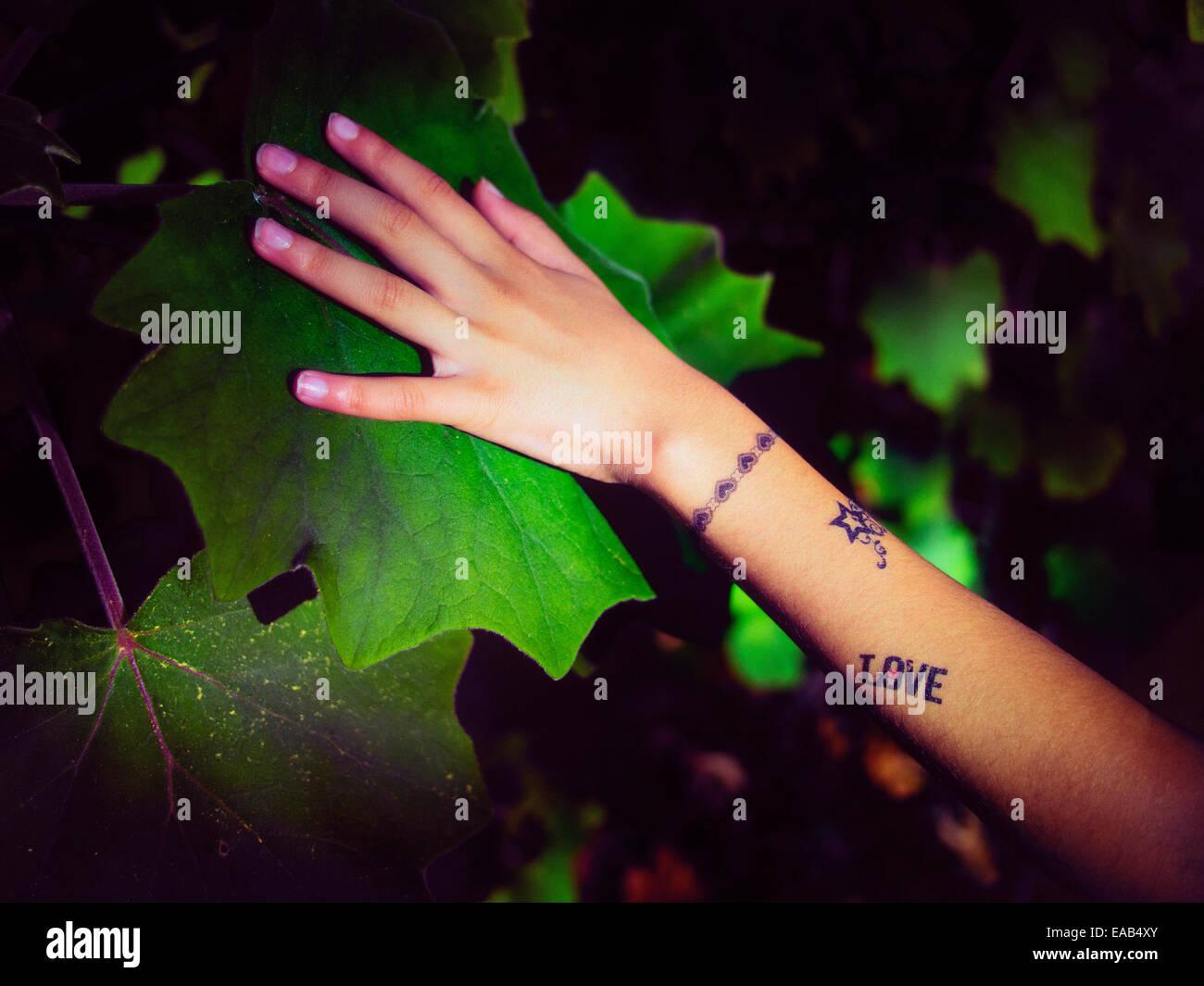 Fille avec le tatouage temporaire met la main sur leaf Banque D'Images