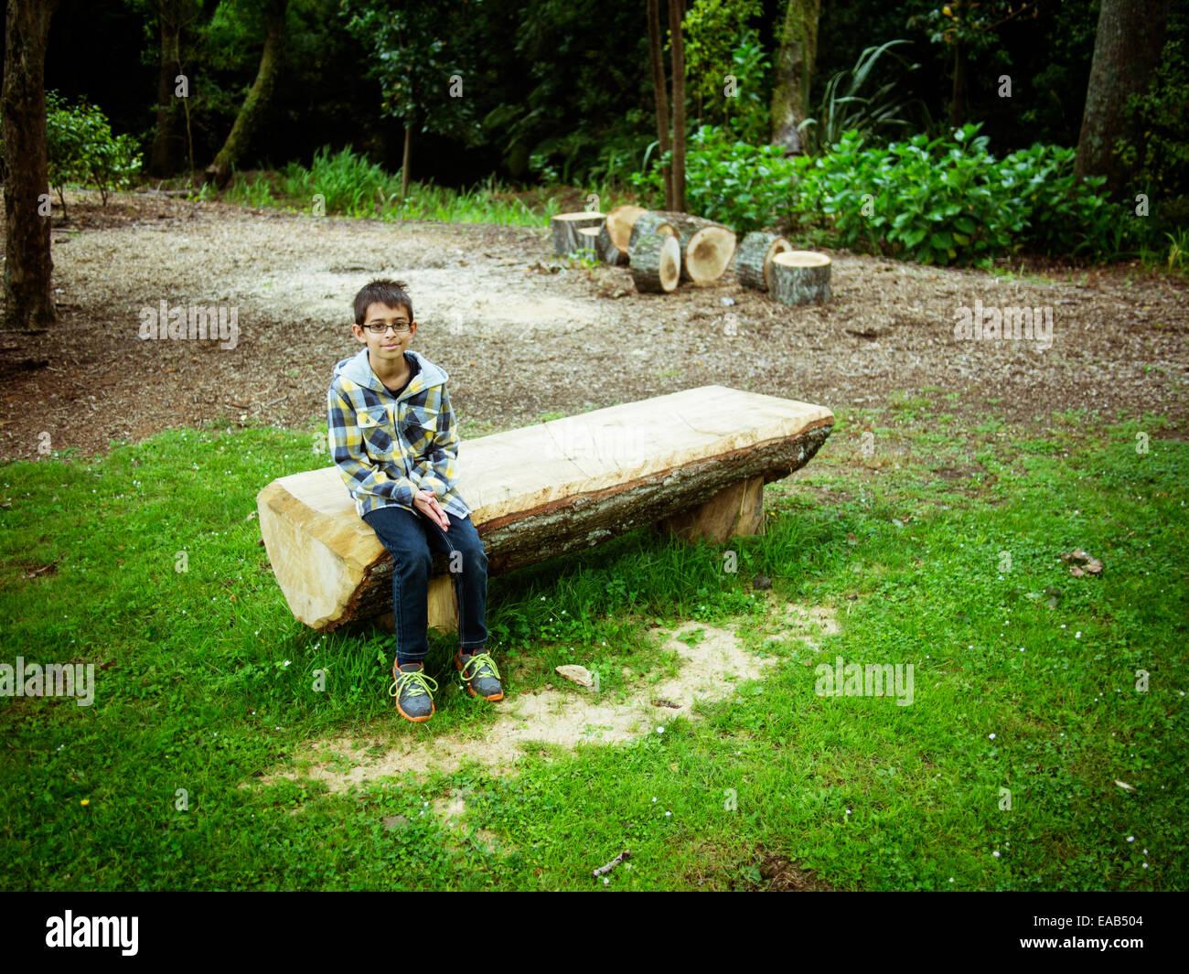 Garçon est assis sur le banc de parc en journal scié Banque D'Images