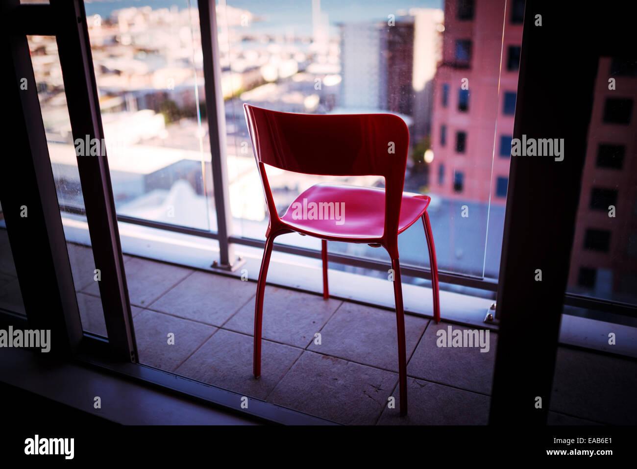 Chaise rouge sur un balcon d'immeuble Photo Stock