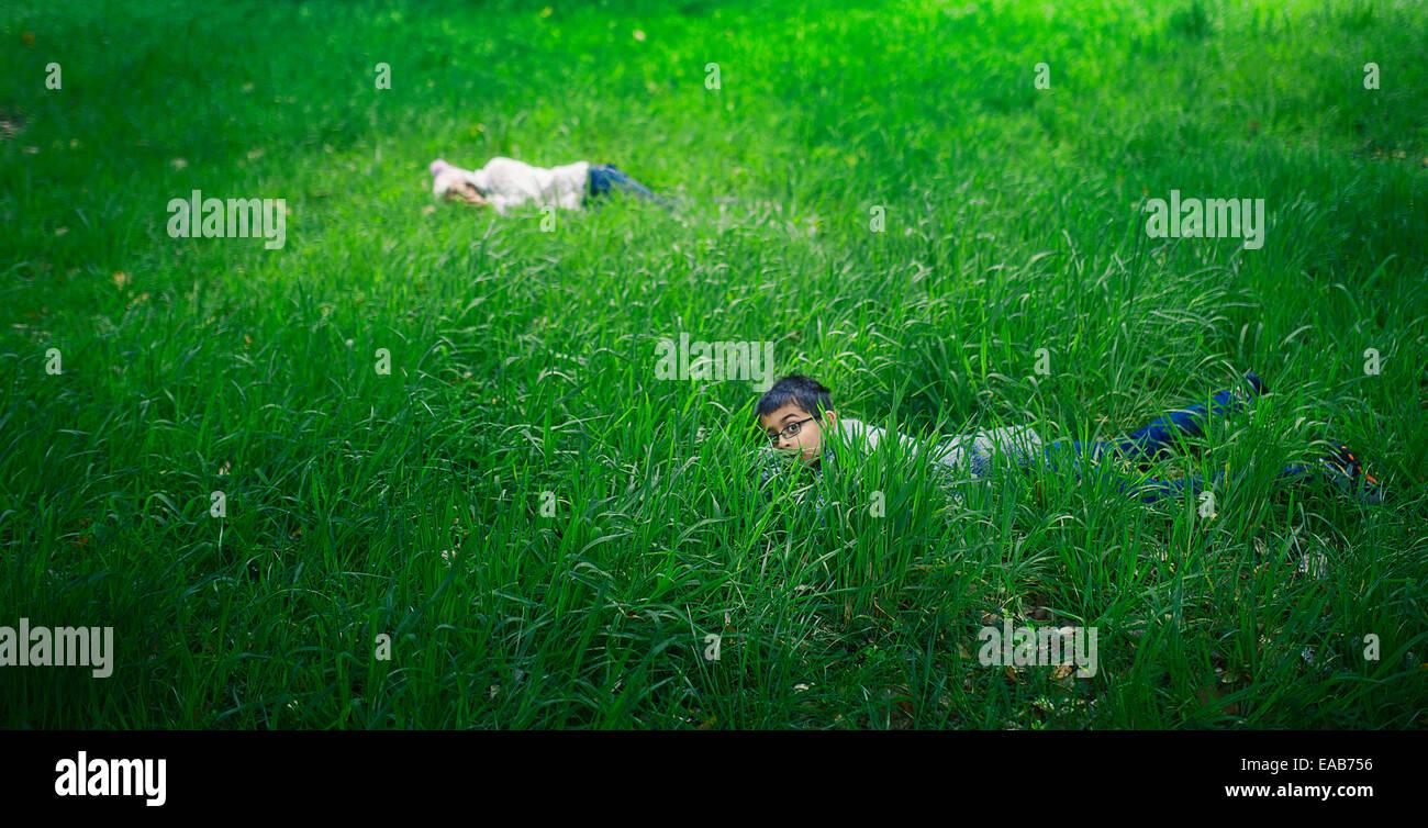 Se cacher dans l'herbe longue. Garçon et fille dans la prairie. Photo Stock