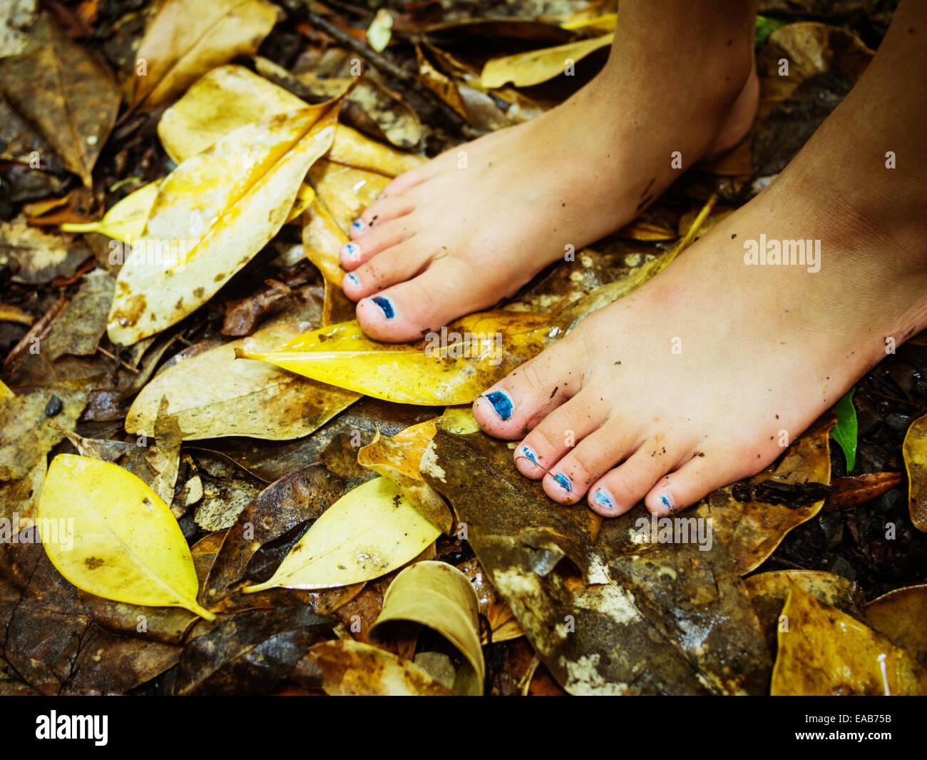 Pieds nus sur les feuilles tombées. Photo Stock