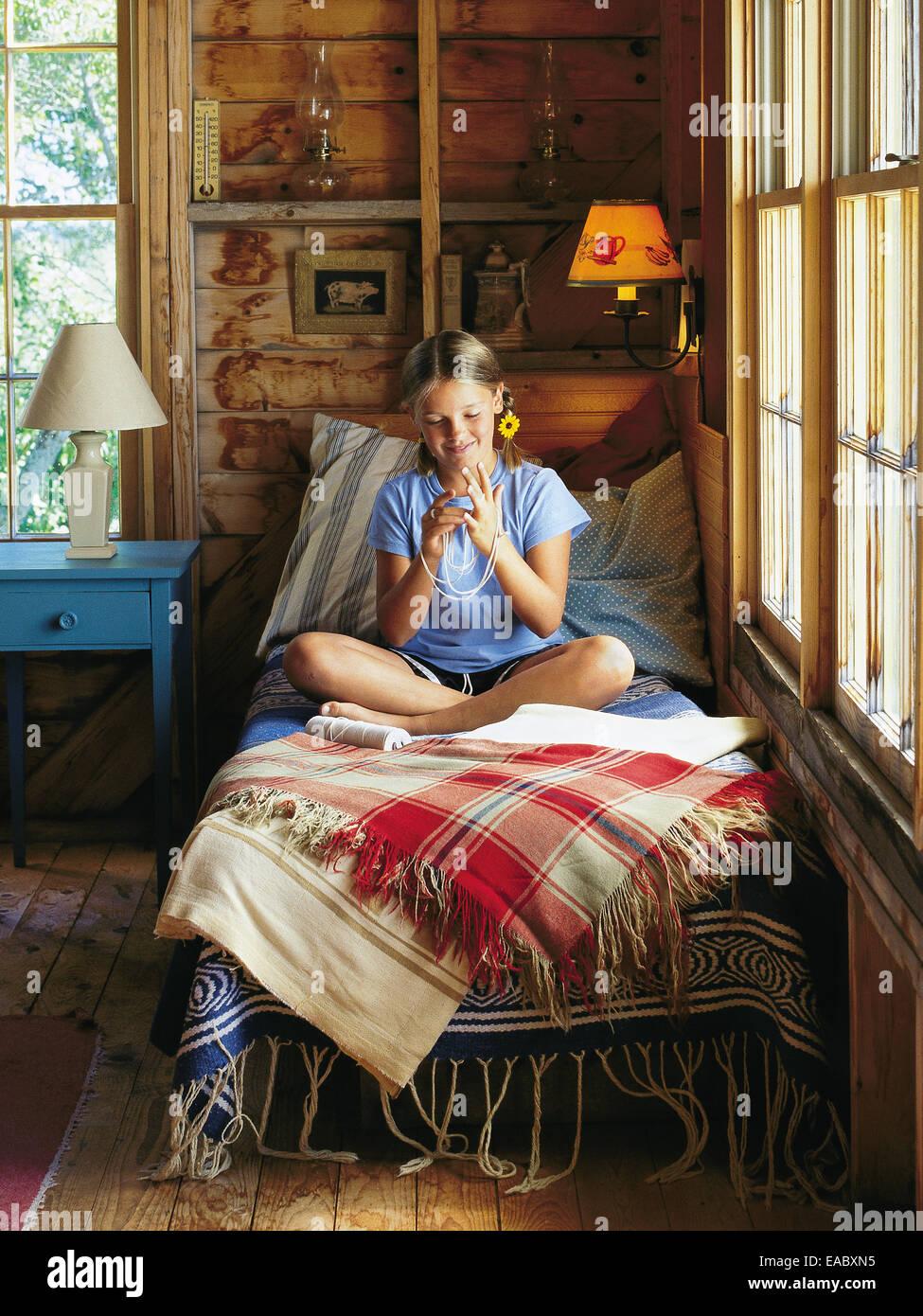 Girl on bed faire cats cradle en pays de montagne Photo Stock