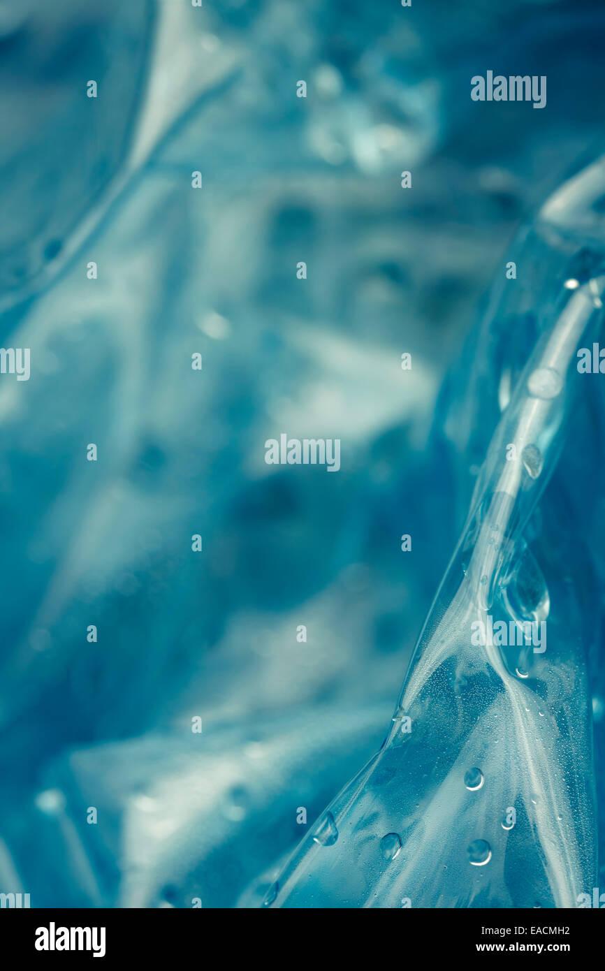 Bouteille d'eau en plastique compressé, gouttes, macro shot, abstract background. Photo Stock