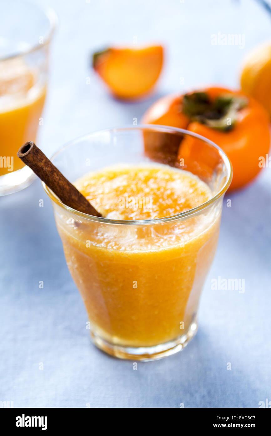 Smoothie orange kaki avec des ingrédients frais par Photo Stock