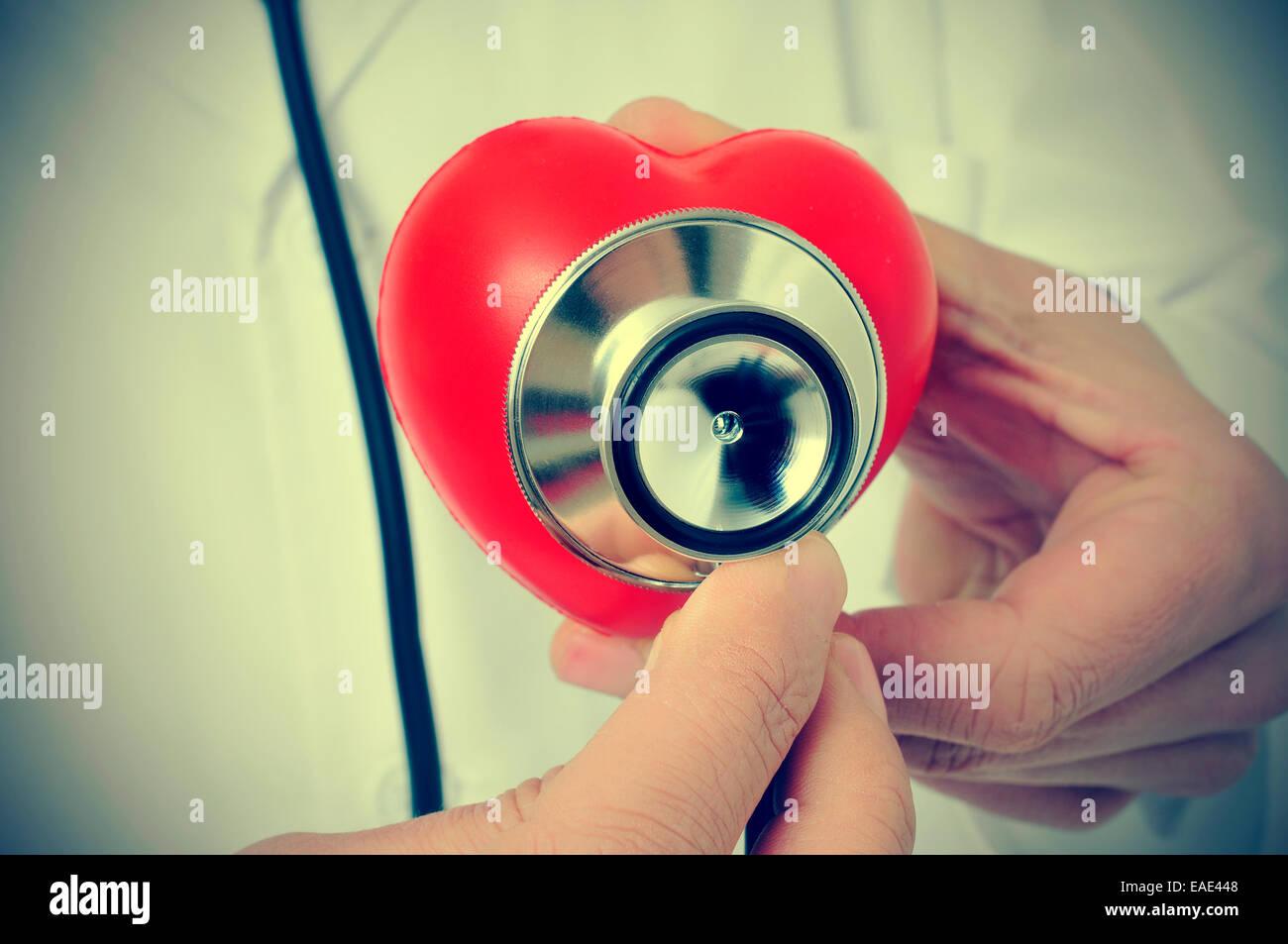 Un médecin auscultating un cœur rouge avec un stéthoscope, avec un effet rétro Photo Stock