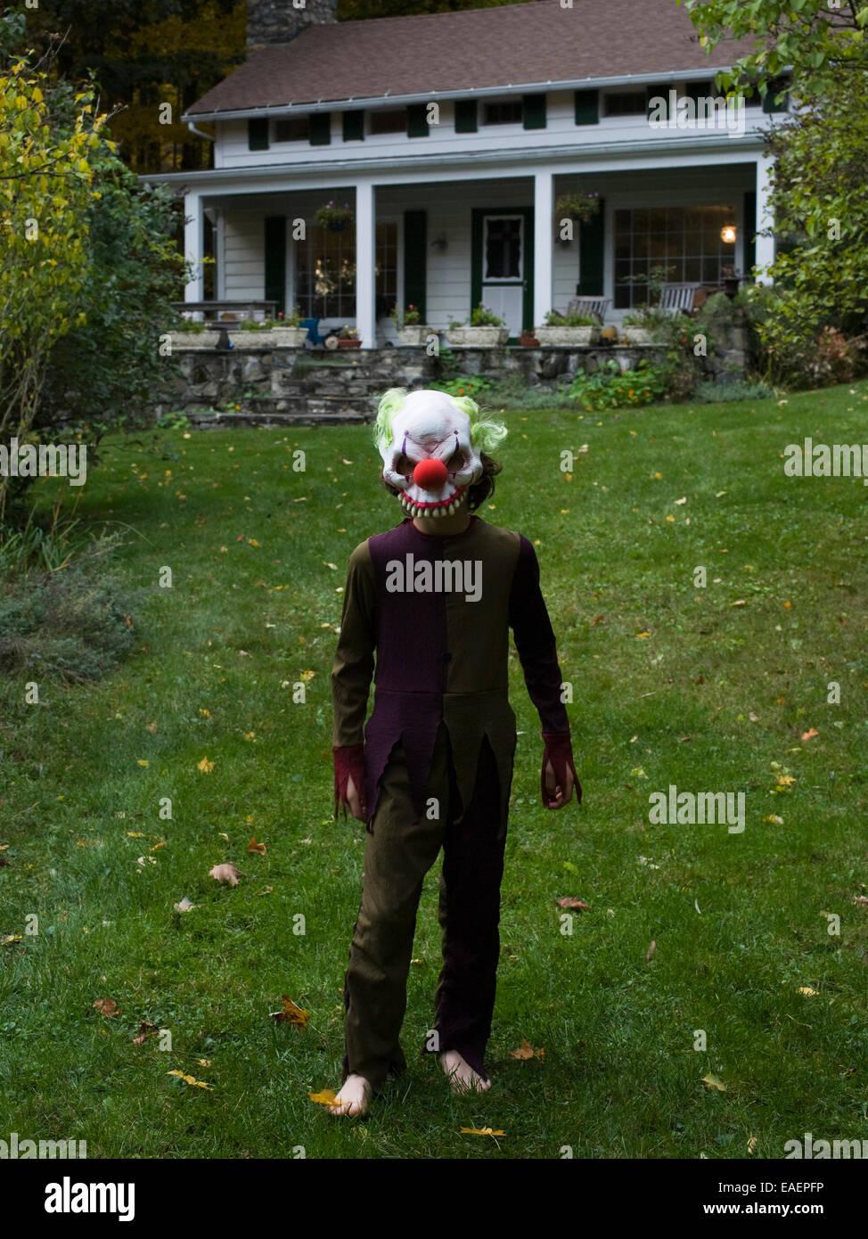 Garçon en costume Halloween et masque sur la pelouse en face de la maison Photo Stock