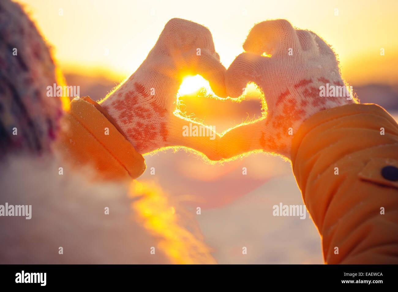 Femme les mains dans des gants d'hiver en forme de symbole du coeur et des sentiments de vie concept avec coucher Photo Stock