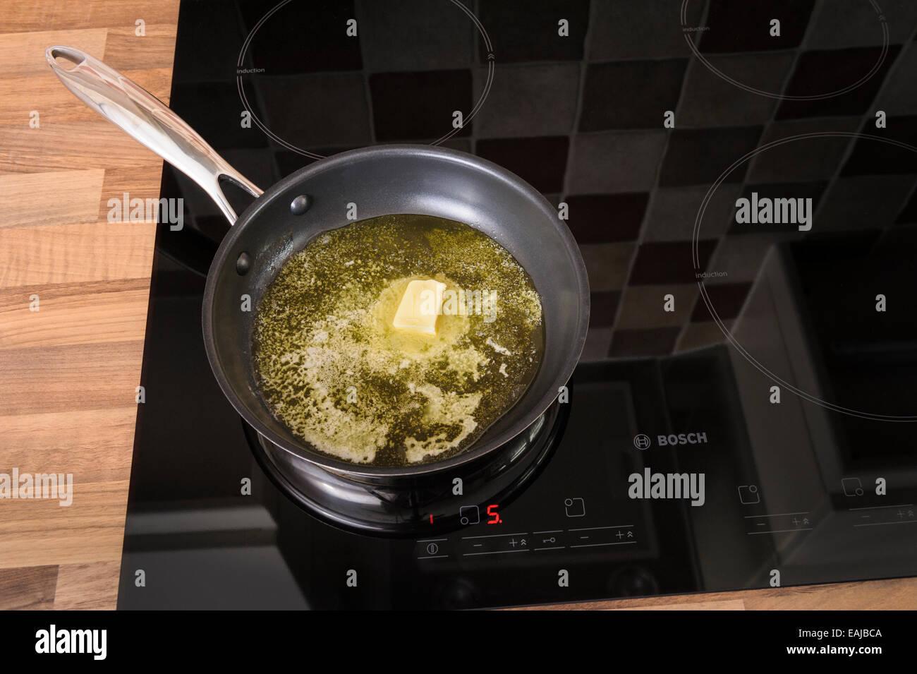 La fonte du beurre dans une poêle, sur une plaque à induction.malsaines, cholestrol. Photo Stock