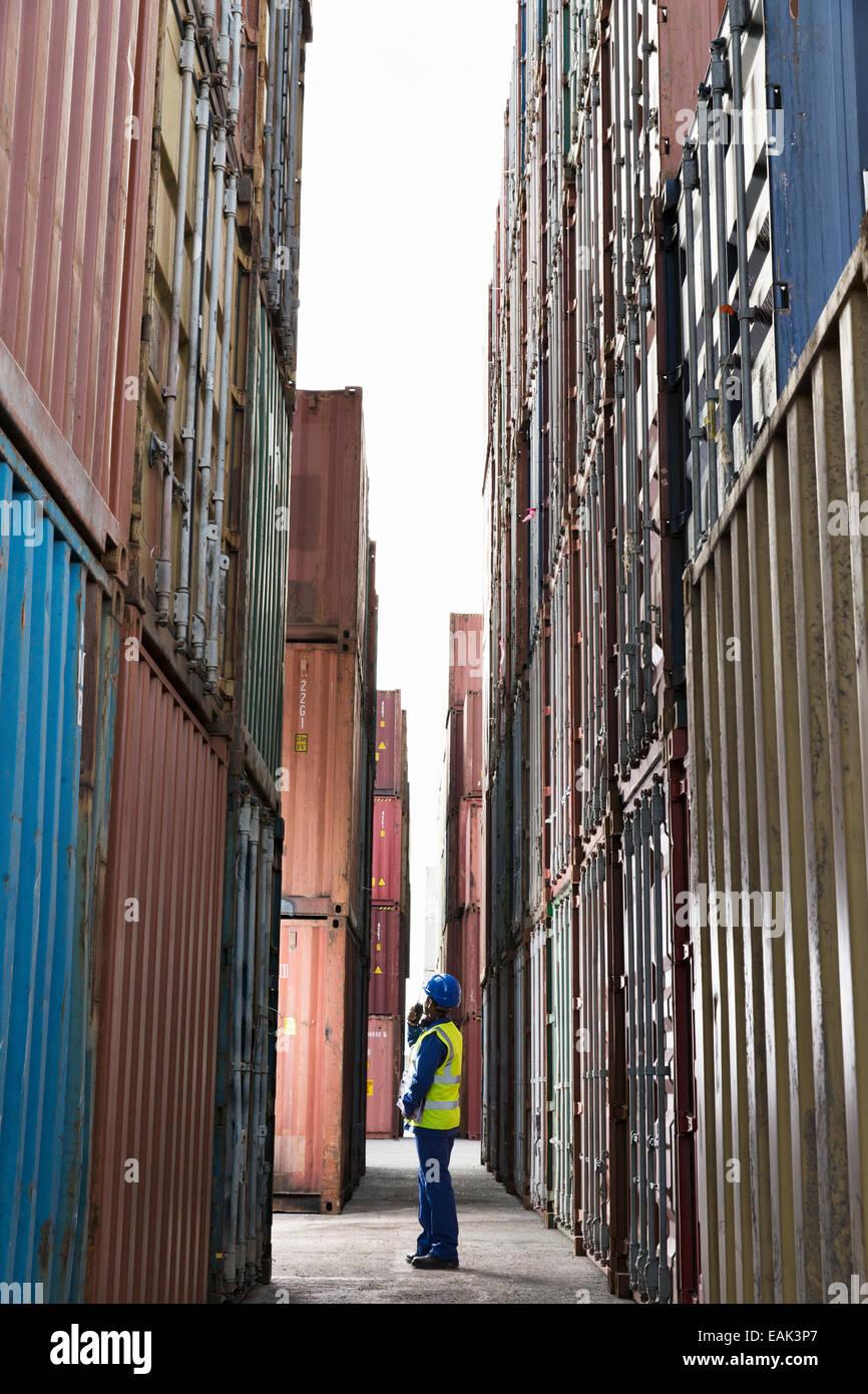 Worker standing entre les conteneurs de fret Photo Stock