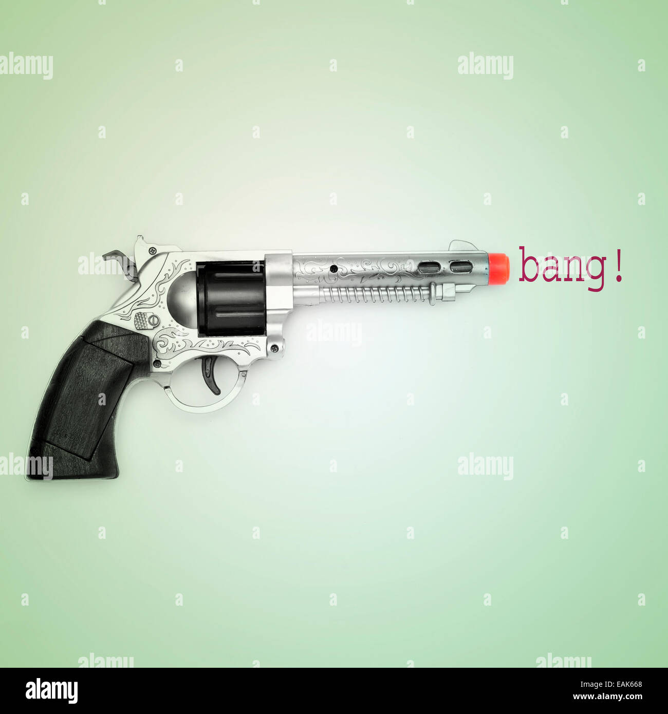 Photo d'un pistolet jouet et le mot bang sur un fond bleu, avec un effet rétro Photo Stock