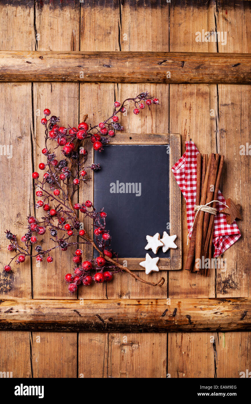Vintage Christmas background with chalk board, branche avec fruits rouges, biscuits de Noël et des bâtons Photo Stock