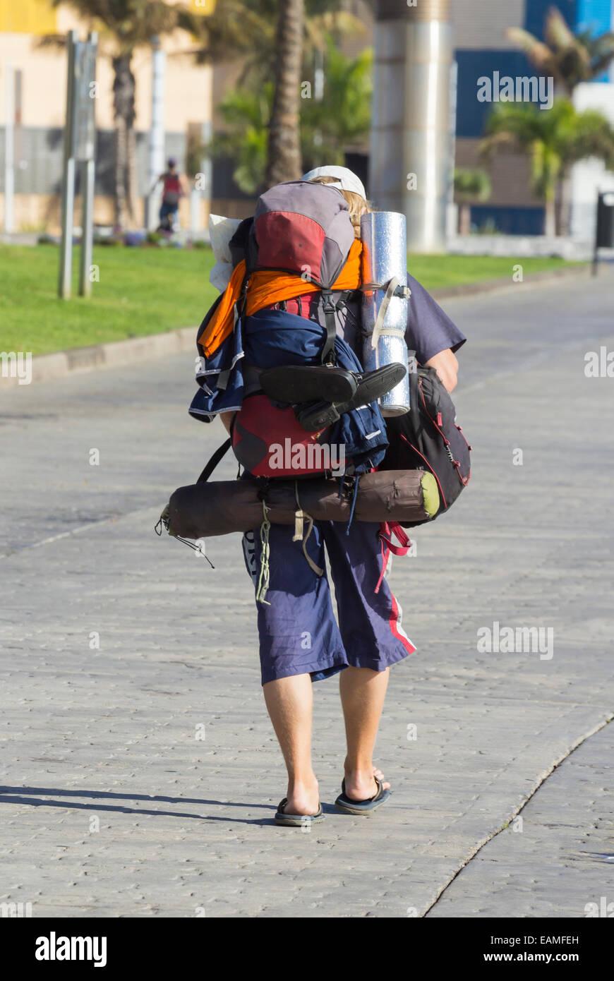 Jeune homme avec un grand sac à dos transportant du matériel de camping en Espagne Photo Stock