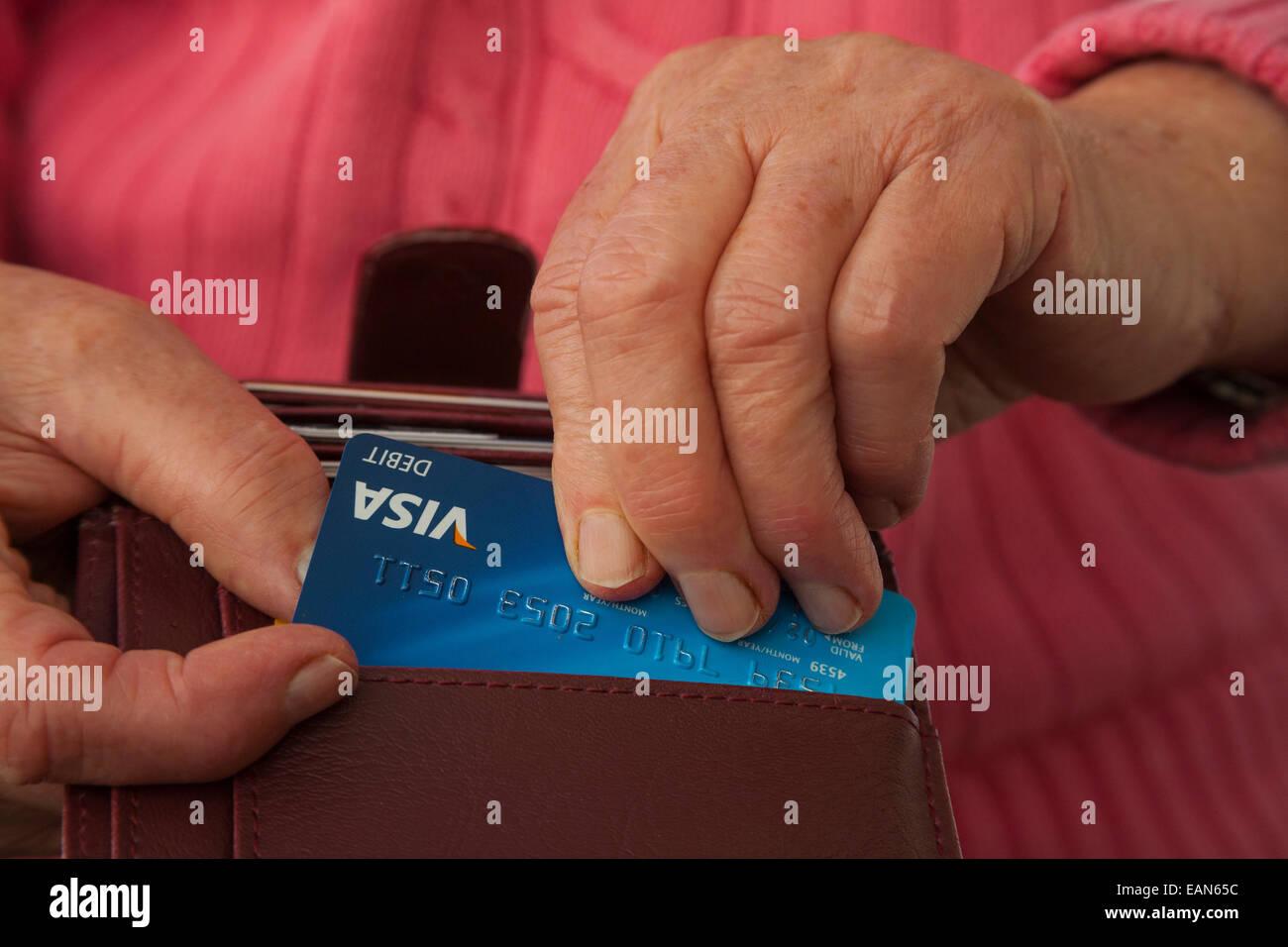 Femme âgée de prendre une carte Visa Débit hors d'un porte-monnaie pour faire une carte d'achat Photo Stock