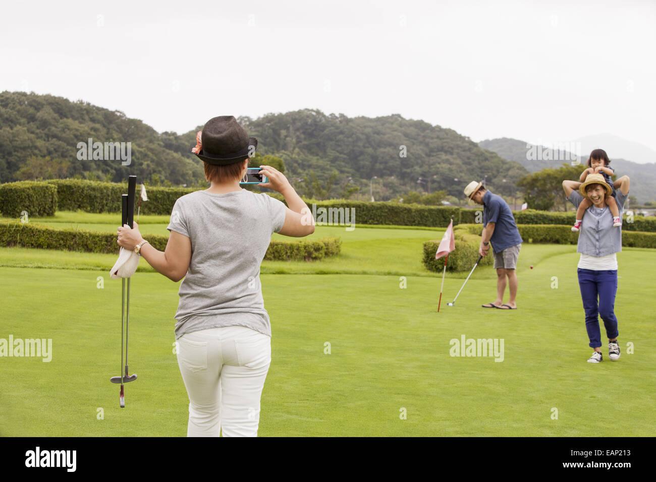 Sur un terrain de golf de la famille.Un enfant et trois adultes. Une femme avec un appareil photo. Banque D'Images
