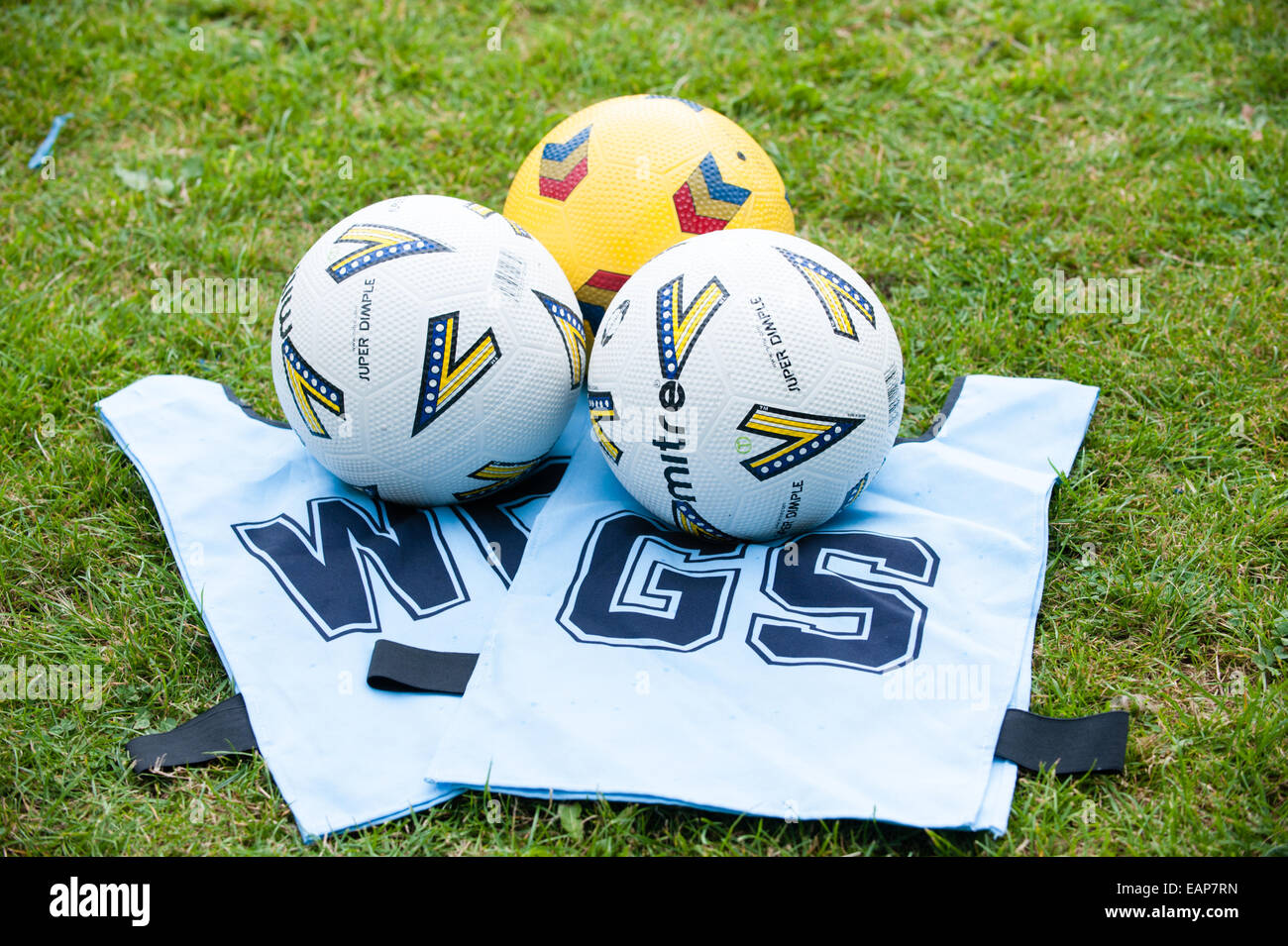 Le netball blanc propre tabards et trois balles de netball sur l'herbe dans une école cours de coaching Photo Stock