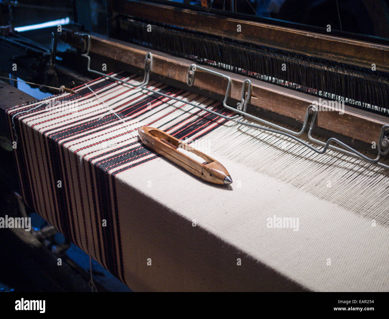 Volant sur un tissu à rayures. Un volant avec la laine blanche repose sur un morceau de tissu à rayures Photo Stock