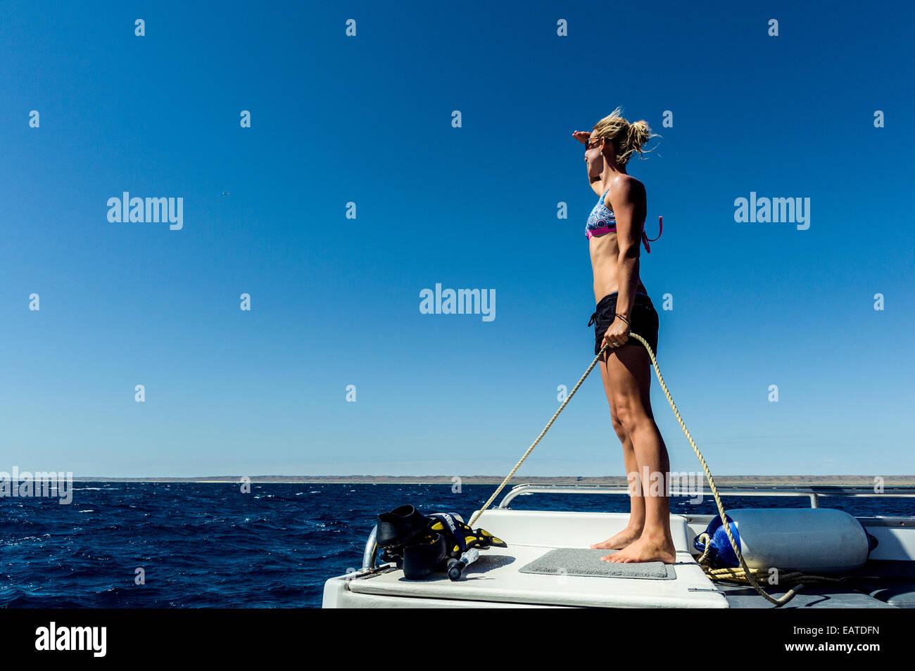 A mettre en place et la jeune femme se tourne vers l'horizon d'un bateau. Photo Stock
