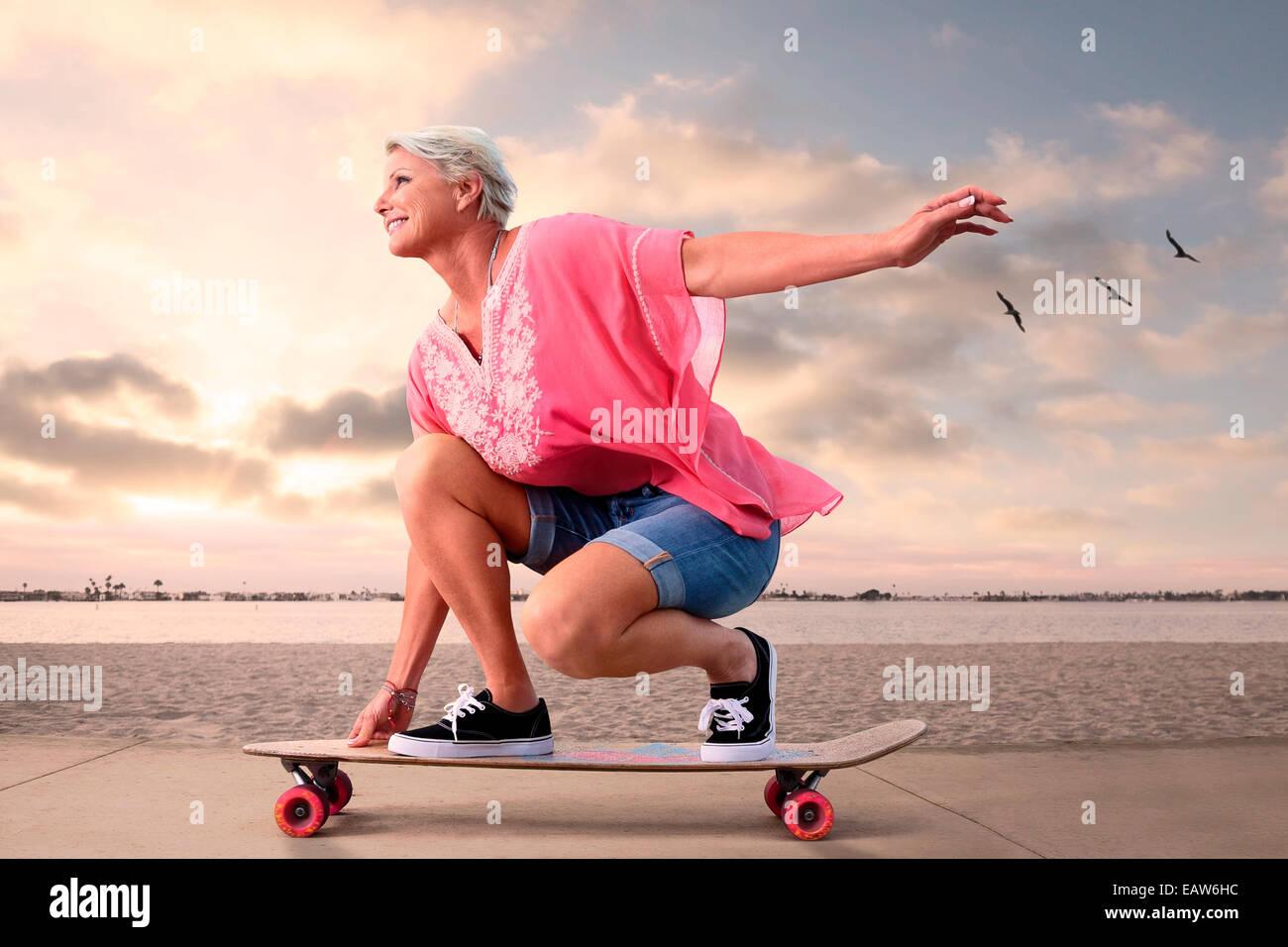 Jeune femme senior sur la planche à roulettes le long de plage au coucher du soleil, les oiseaux volant dans Photo Stock