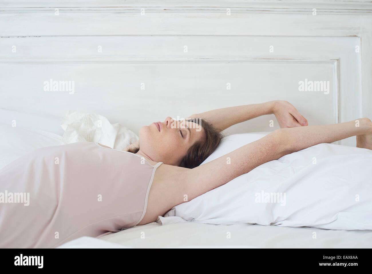 Femme allongé sur le dos dans le lit s'étend Photo Stock