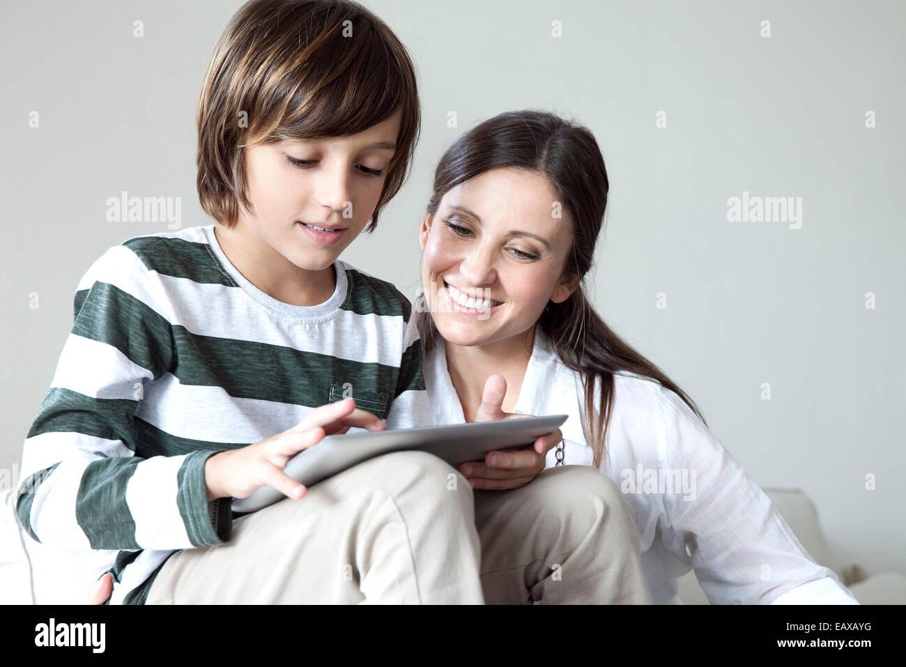 Mère et fils using digital tablet together Photo Stock