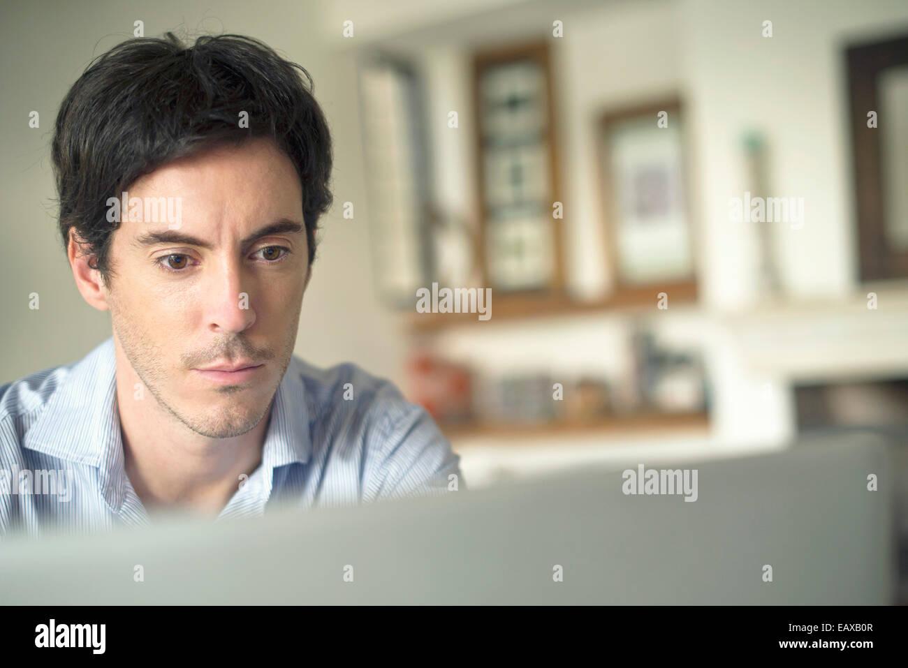 L'homme regardant l'ordinateur portable Photo Stock