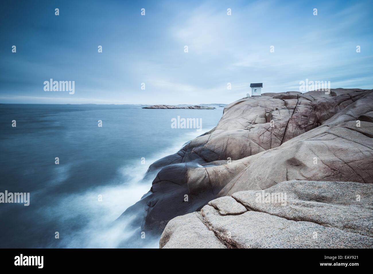 Cabine sur falaise près de la mer avec ciel dramatique Photo Stock