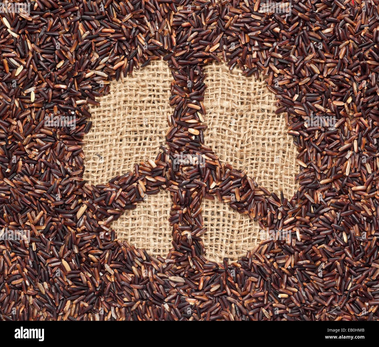 Riz rouge formant un symbole de paix sur tissu jute Photo Stock