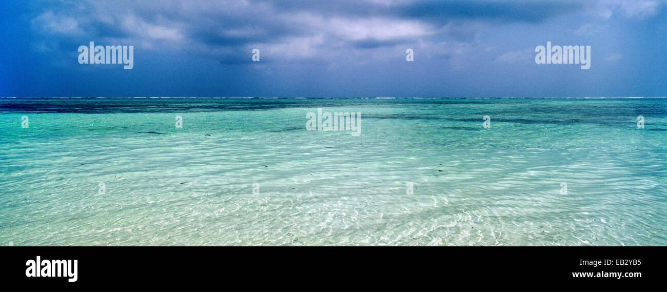 Une tempête tropicale s'approche de la ligne d'un récif à l'horizon de calme mer turquoise. Photo Stock