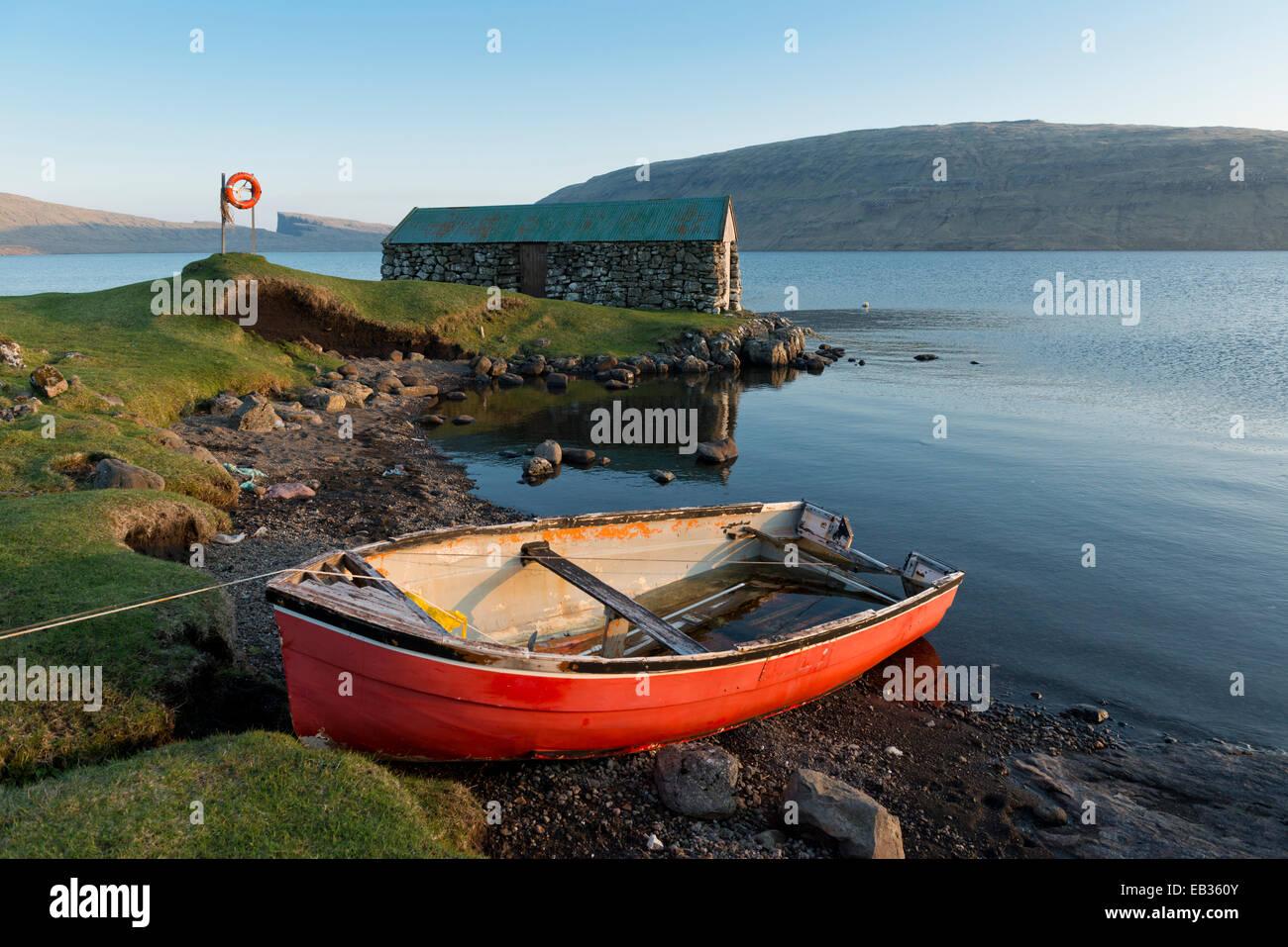 Bateau rouge en face d'une maison de bateau sur le lac ou Sørvágsvatn Leitisvatn, Pigalle, îles Photo Stock