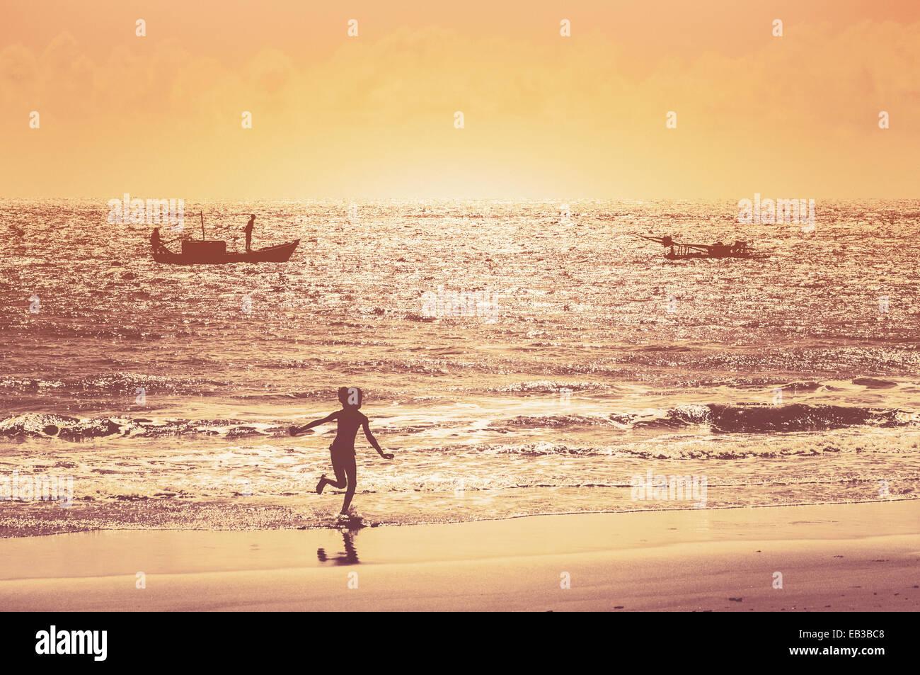 Brésil, Pirangi, Rio Grande do Norte, fille courir sur la plage pendant le coucher du soleil Photo Stock