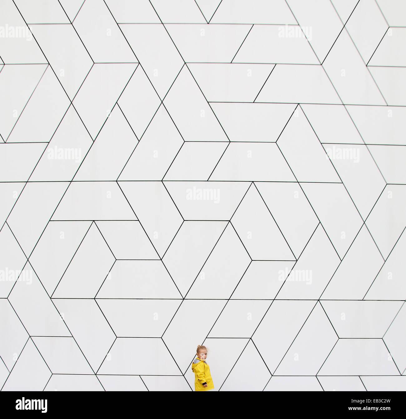 Girl (2-3) en imperméable jaune contre mur blanc Photo Stock