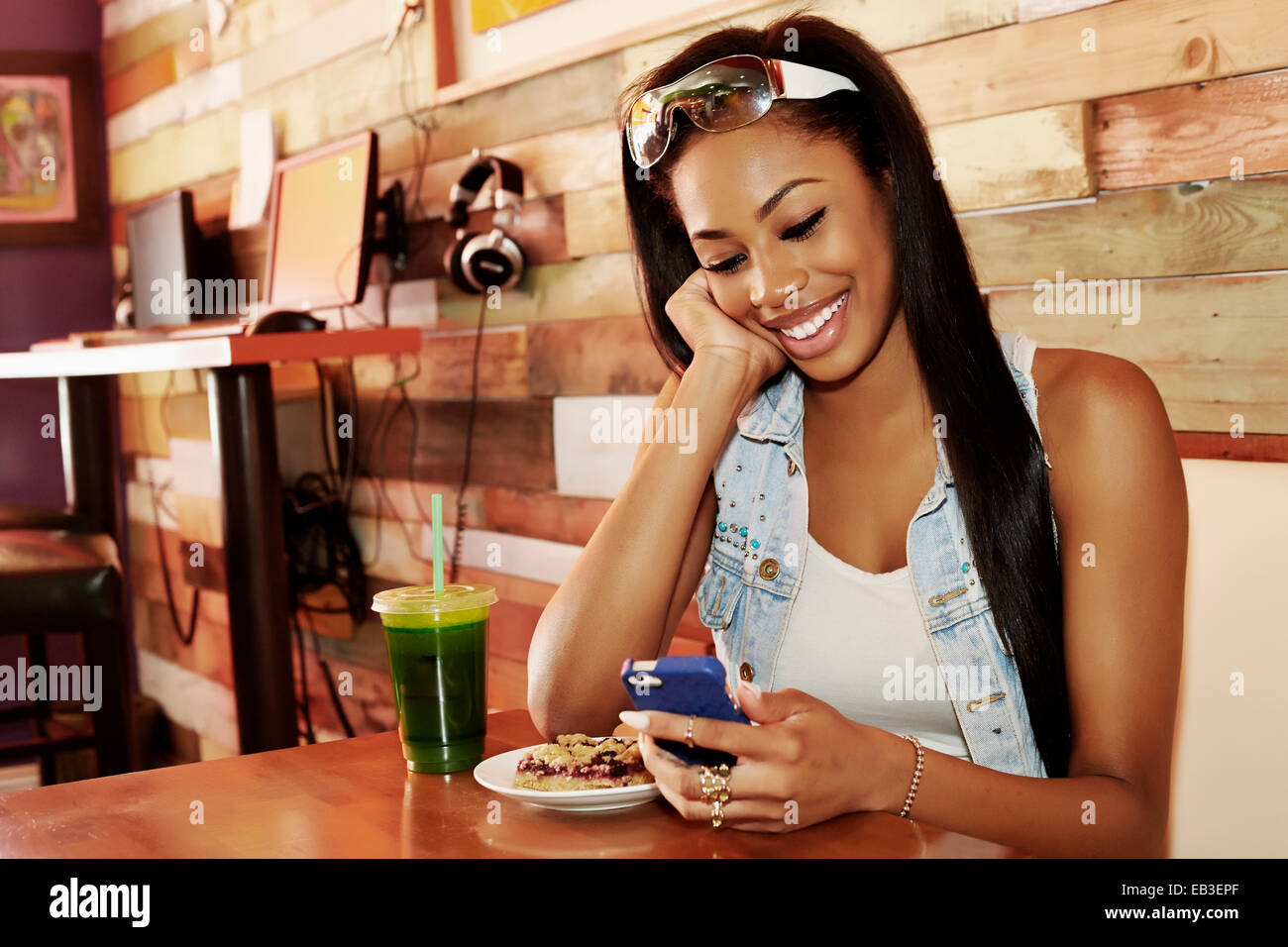 African American Woman using cell phone in cafe Banque D'Images