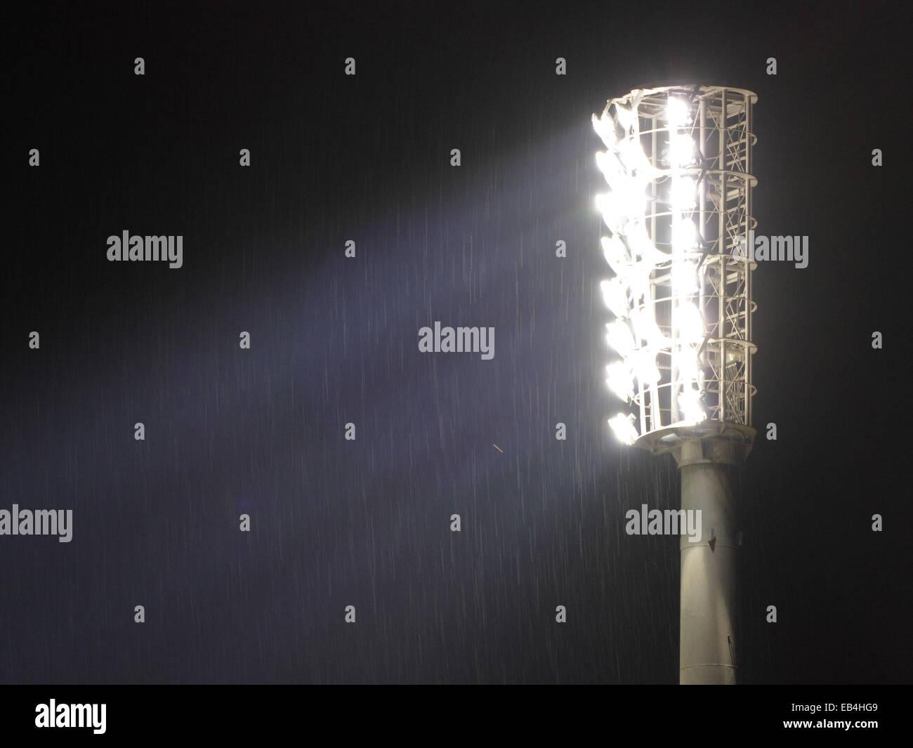 Les projecteurs du stade dans la nuit rougeoyante Photo Stock