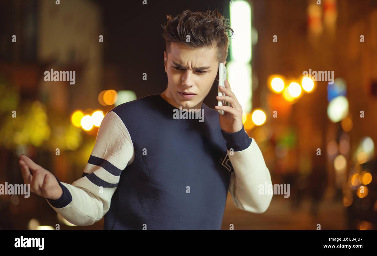 Jeune homme calme à parler au téléphone Photo Stock