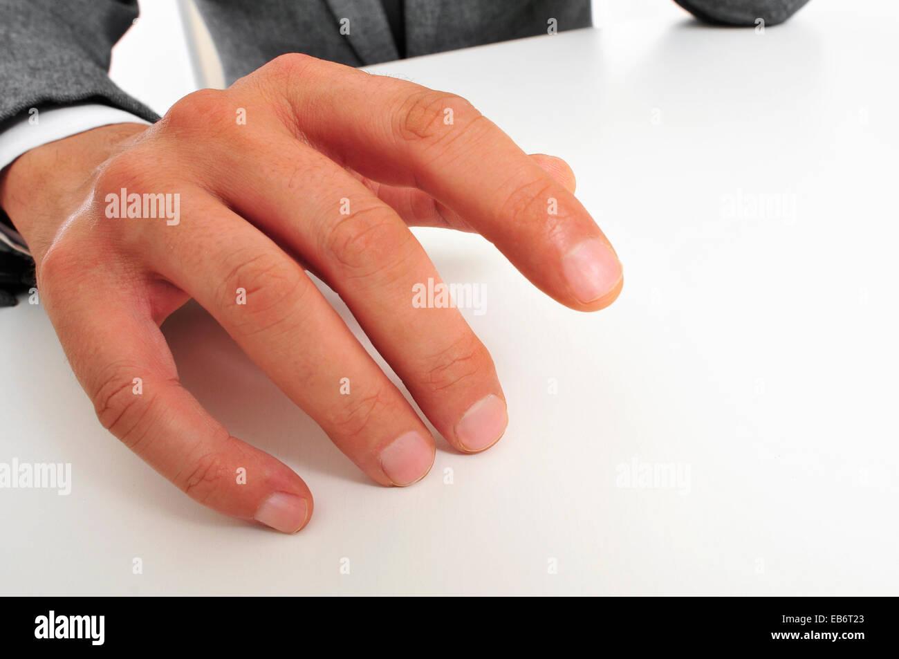 Homme portant un costume sitting drumming ses doigts sur le bureau Photo Stock
