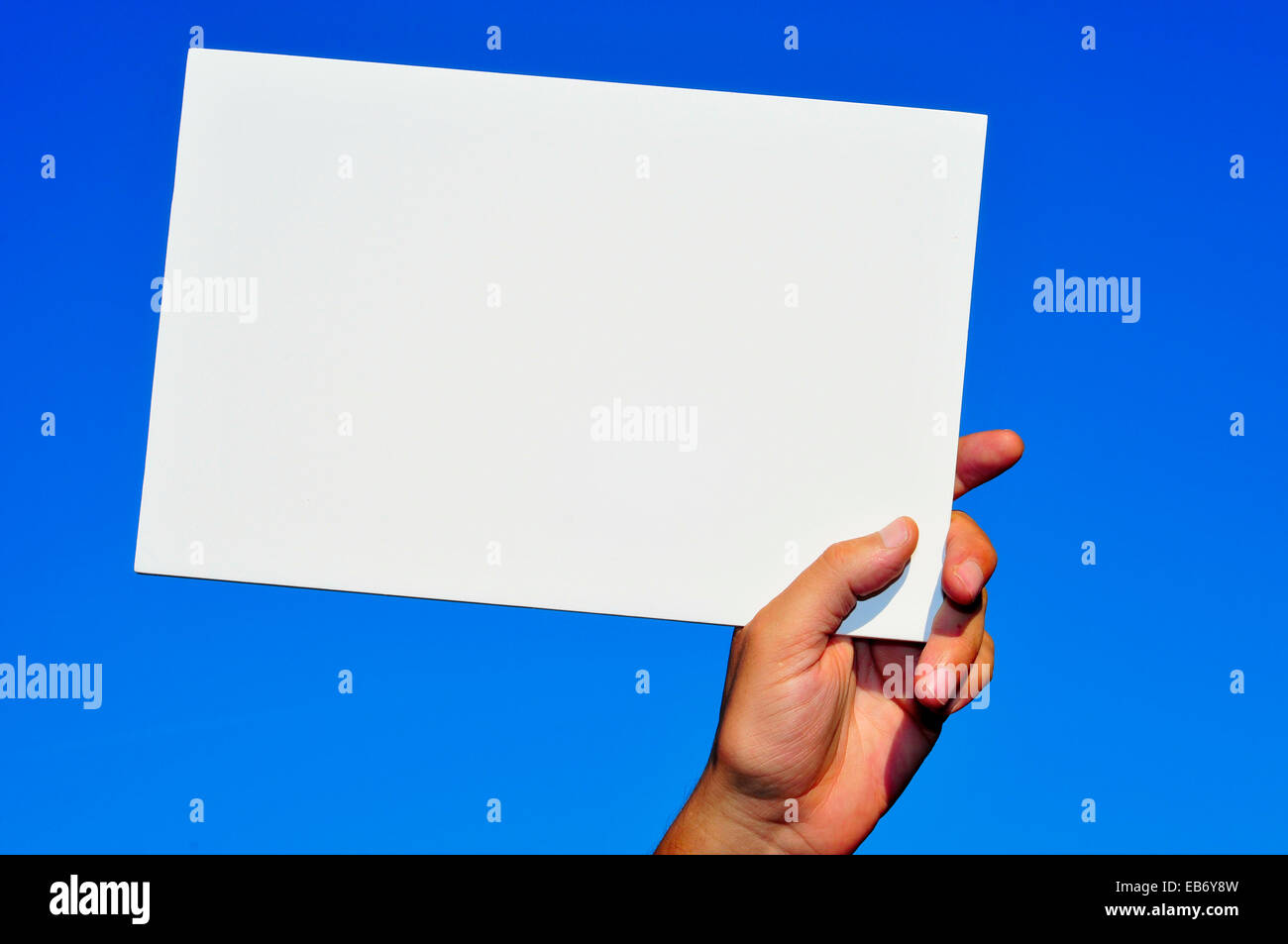 La main d'un homme tenant une pancarte blanche avec une copie-espace sur le ciel bleu Banque D'Images