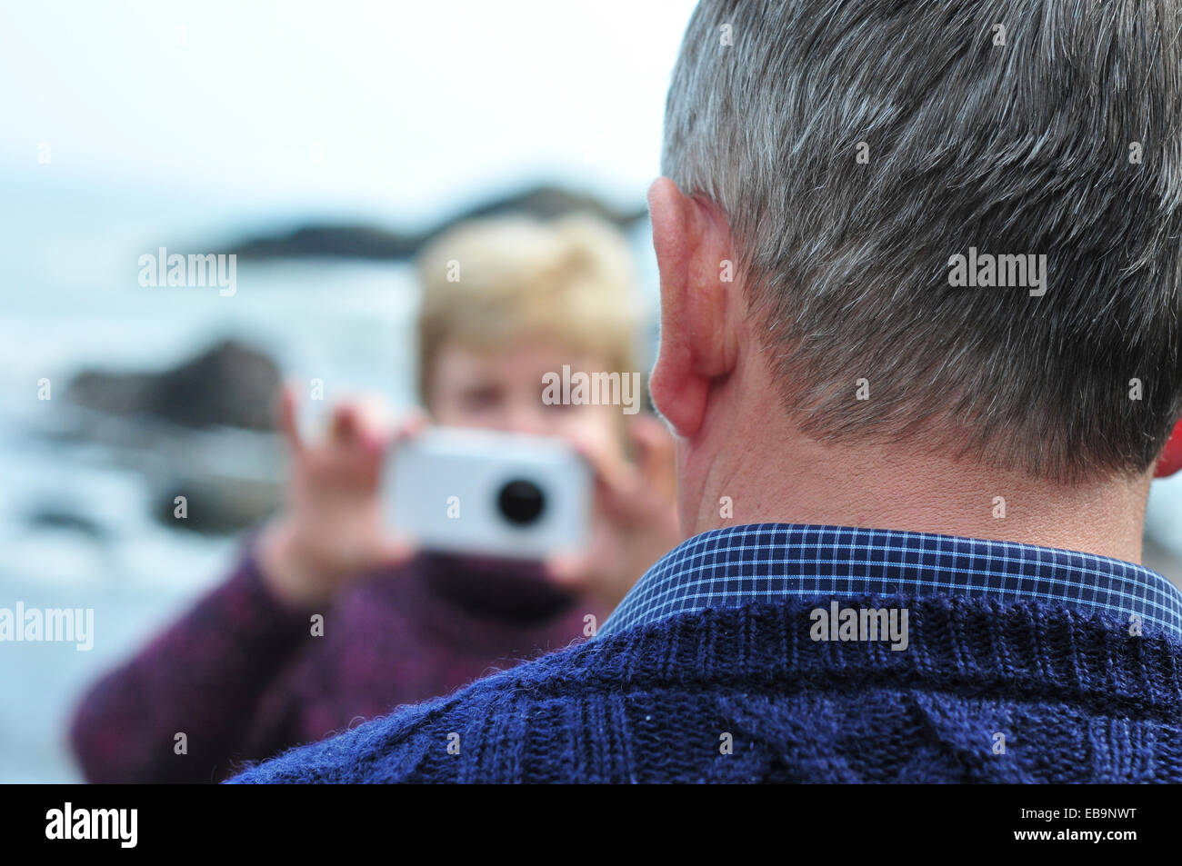 Woman Taking Photo of Man with Smart Phone Banque D'Images