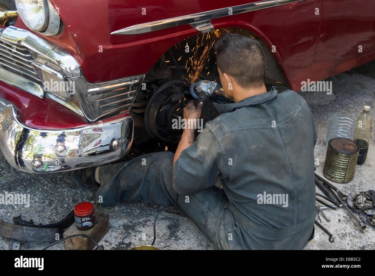 Mécanicien de voiture tente de réparer un classique cubain sur la rue. La Havane, Cuba. Photo Stock