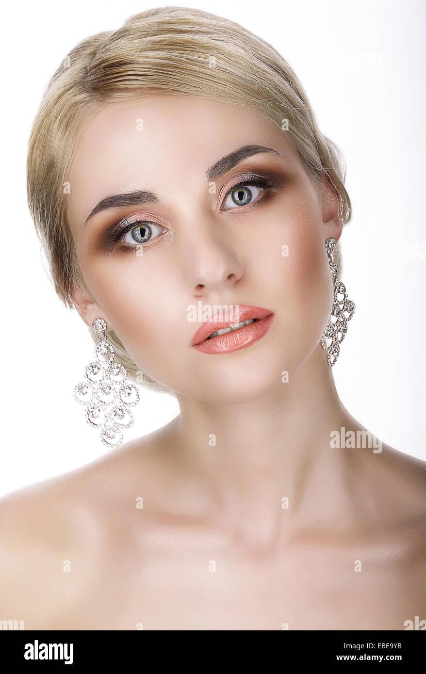 Le magnétisme. Portrait of Young blonde avec des boucles d'oreilles brillant Photo Stock