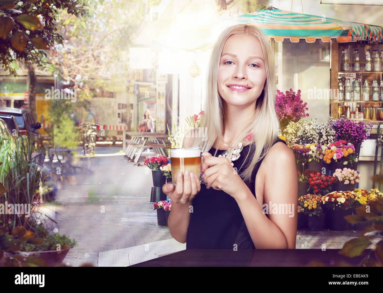 Vous pourrez vous rafraîchir. Femme heureuse avec tasse de café dans un café de la rue Photo Stock
