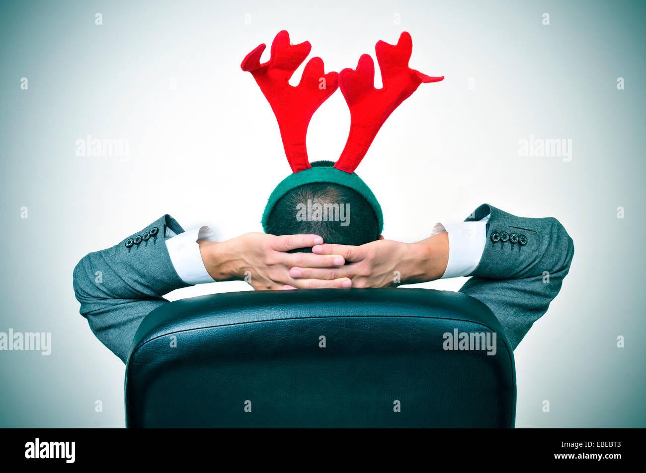 Un homme avec un bandeau reindeer antlers se détendre dans son bureau de président après un party Photo Stock