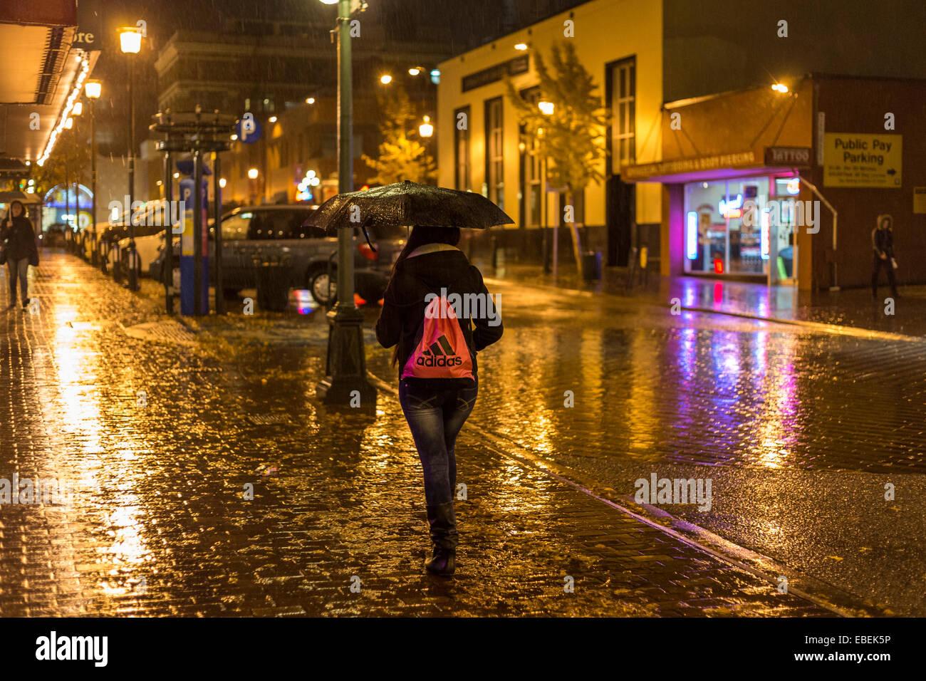 Jeune femme marchant à travers le centre-ville de nuit pluvieuse-Victoria, Colombie-Britannique, Canada. Banque D'Images