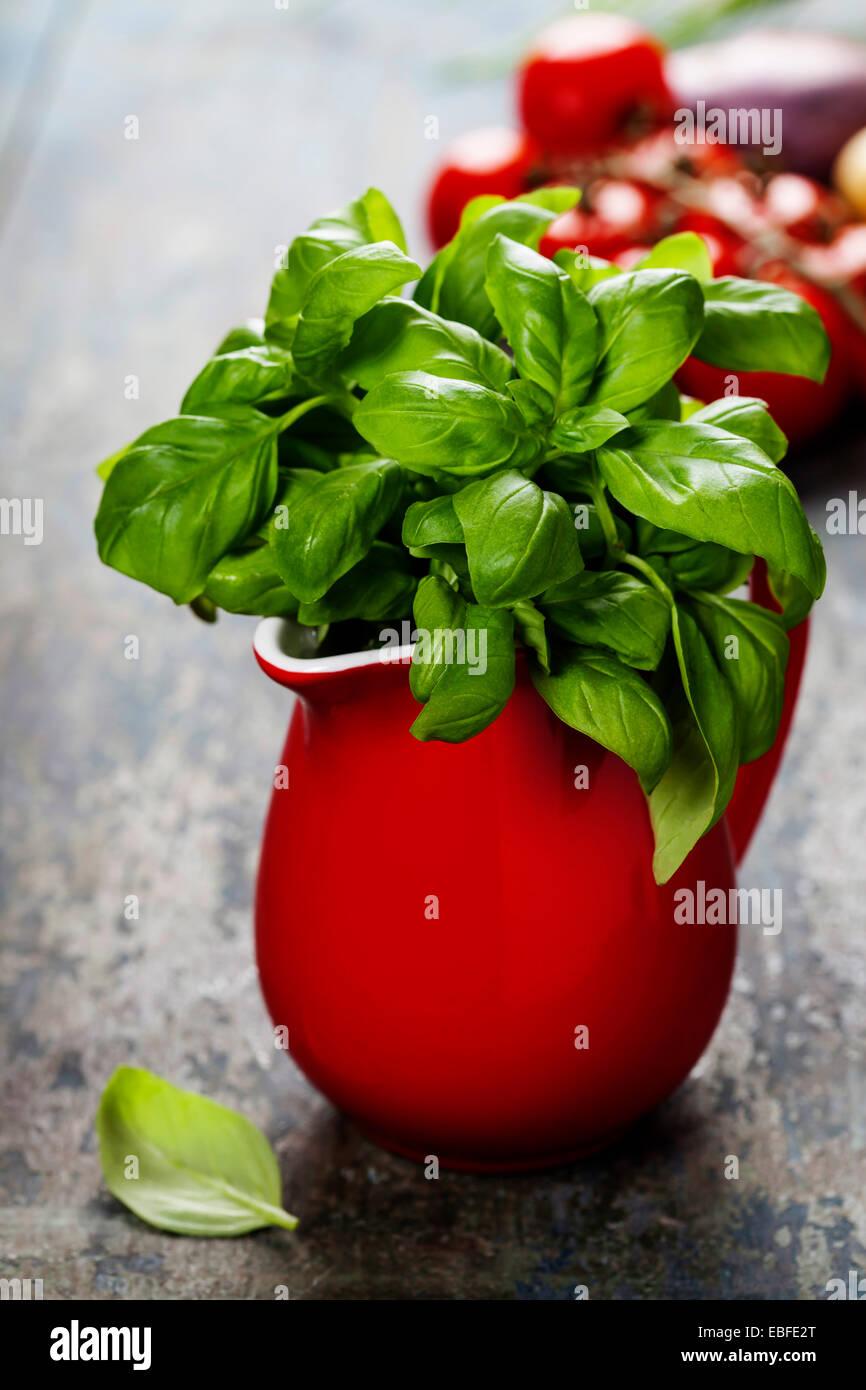 Le basilic frais en pichet rouge avec des ingrédients. L'alimentation biologique, de la santé ou la Photo Stock