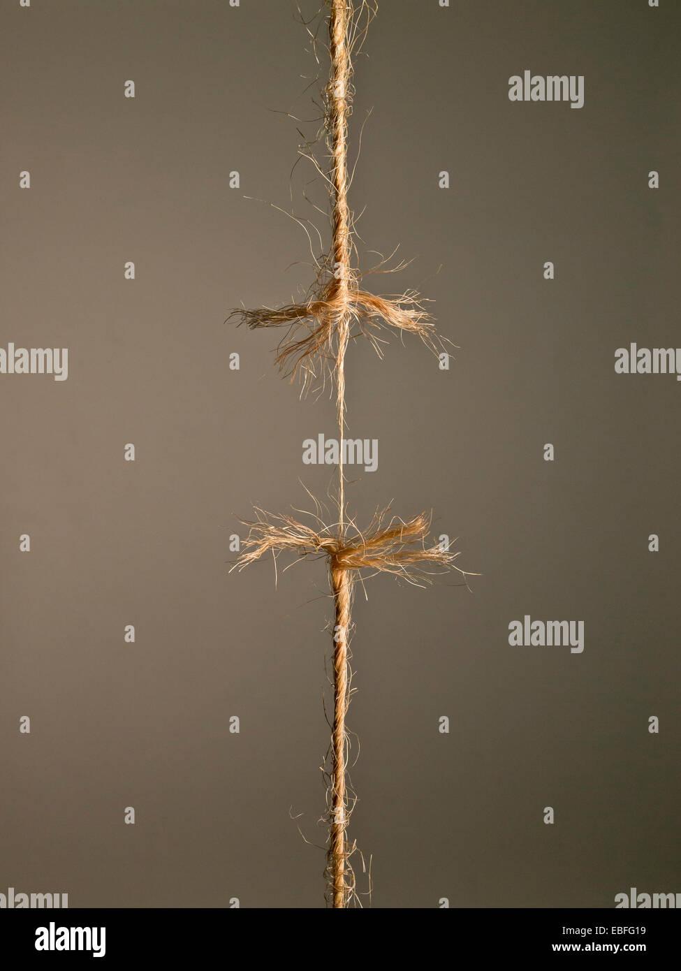 Sous la tension de la corde, le moment avant de se séparer sur fond brun Photo Stock