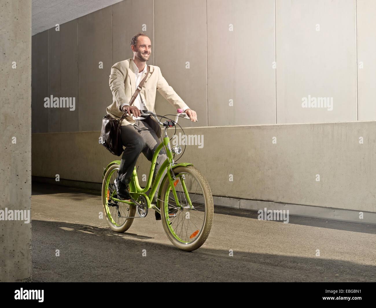 Homme portant un sac sur son épaule, tout en faisant du vélo dans la ville, Innsbruck, Tyrol, Autriche Photo Stock