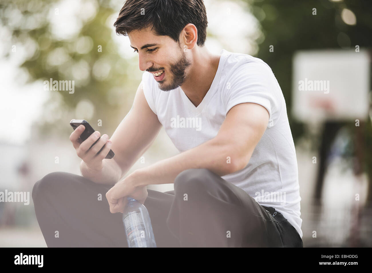 Jeune homme basket-ball la lecture de textes sur le smartphone. Photo Stock