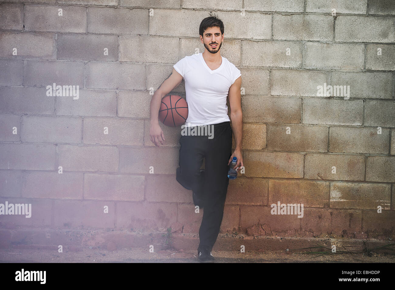 Jeune joueur de basket-ball masculin leaning against wall Photo Stock