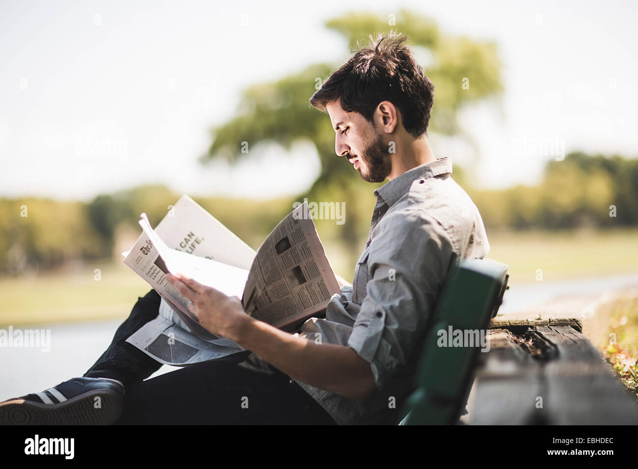 Young man reading newspaper on park bench Photo Stock